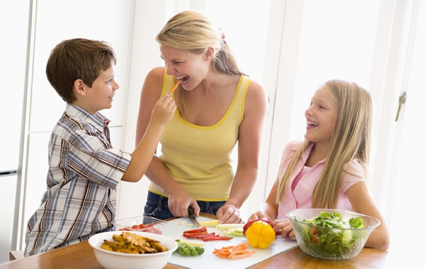 mom with kids preparing salad