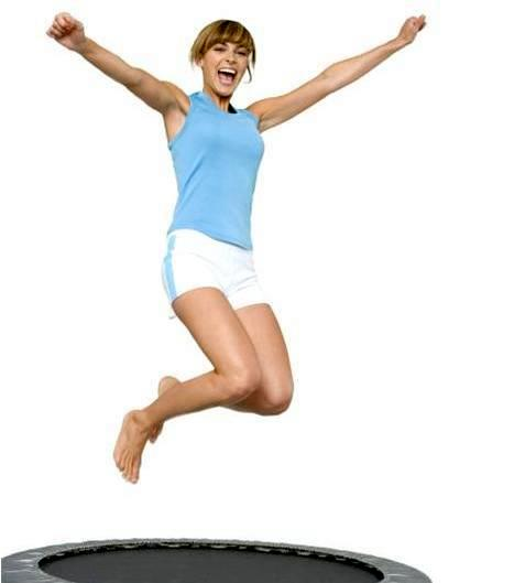 Young woman jumping on trampoline, low angle view